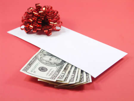 envelope with US twenty dollar bills and a red bow isolated on red. shallow depth of field. focus on money. Stock Photo - 259445