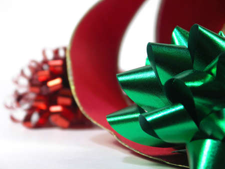 red and green bow with curling red ribbon isolated on white. shallow depth of field. focus on green bow.