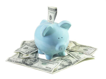 U.S. one hundred dollar bill stuck partially into a blue ceramic piggy bank sitting in a pile of money. Isolated on white. Shallow depth of field. Focus on top of bill. 写真素材