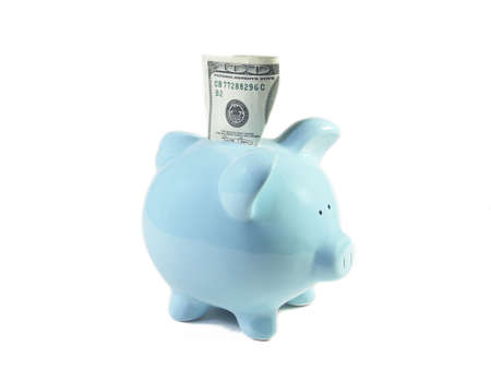 U.S. one hundred dollar bill stuck partially into a blue ceramic piggy bank. Isolated on white. Shallow depth of field. Focus on top of bill. Stock Photo