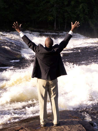 liberating: business man in a suit standing in front of a rushing river with hands raised in a triumphant gesture Stock Photo