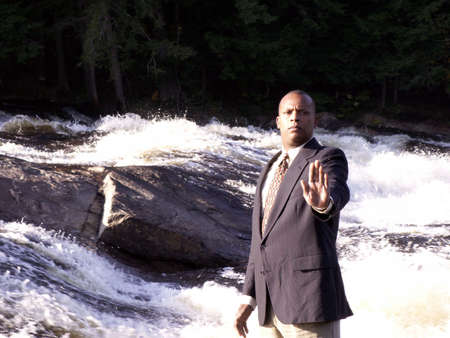 business man in a suit in front of rushing river with hand held out. photo