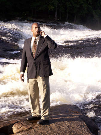 business man in a suit with cell phone standing on a rock in front of a river photo