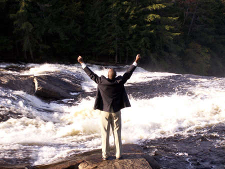 liberating: business man in a suit with cell phone standing in front of a rushing river with fists raised in a triumphant gesture Stock Photo