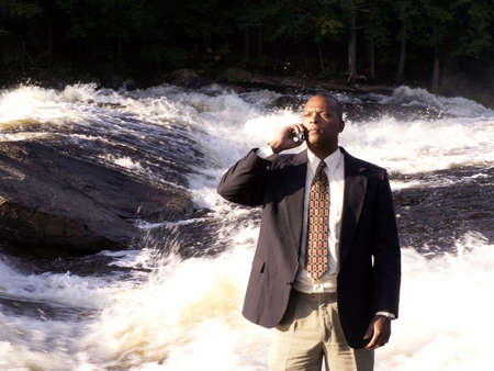business man in a suit with cell phone standing in front of a rushing river photo