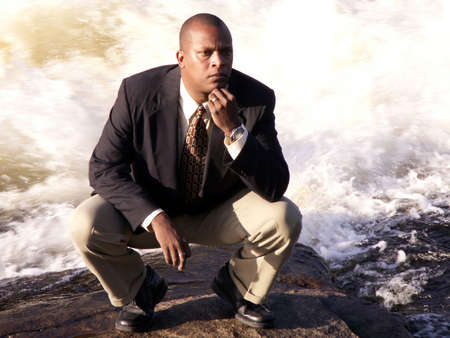 squatting down: business man in a suit squatting down thinking in front of a rushing river
