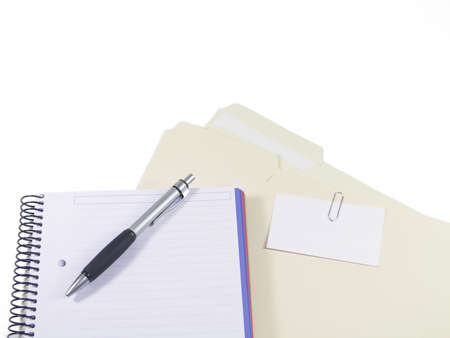 a pen, blank notebook and folders with business card paperclipped to outside with pages showing Stock Photo