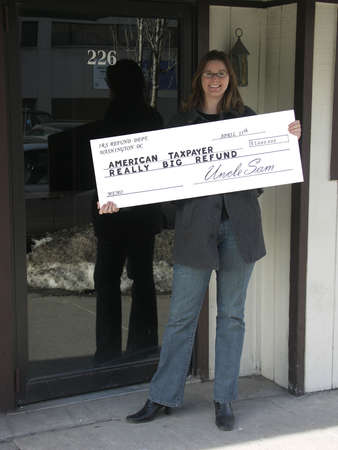 Smiling woman holding an oversize tax refund check. Focus on the check.