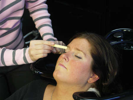 A woman gets her eyebrows waxed.