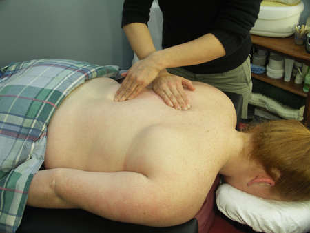 masseuse: A woman getting a massage. The focus is on the hands of the masseuse.