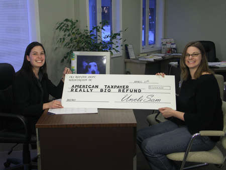 A surprised woman receives an oversized tax refund check. photo