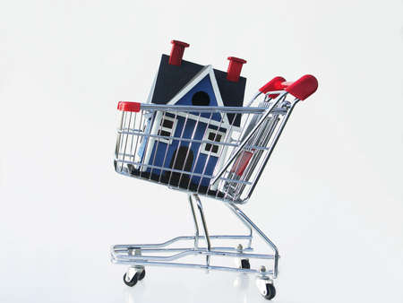 Miniature house in a shopping cart isolated on white illustrating shopping for a home.