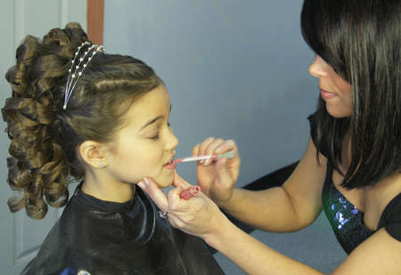 A young girl gets lip gloss applied by a stylist at a salon. Focus on top of young girls face. Motion blur intentional on stylists hand.