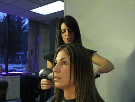 A woman gets her hair colored at the salon. Stock Photo