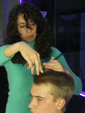 Hair stylist cutting young mans hair. Focus is on the stylists hand with the scissors in it. Intentional motion blur on the stylists body. Stock Photo