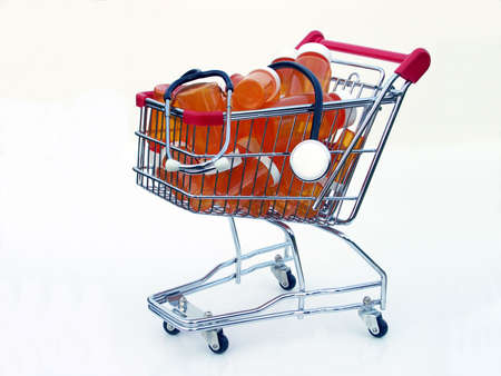 Miniature shopping cart isolated on white filled with prescription bottles and a stethoscope illustrating shopping for a health care provider or pharmacy. Stock Photo