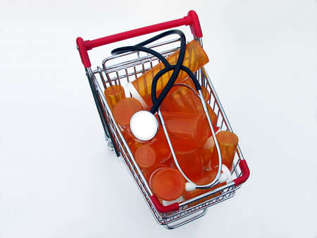 ailment: Miniature shopping cart isolated on white filled with prescription bottles and a stethoscope illustrating shopping for a health care provider or pharmacy. Stock Photo