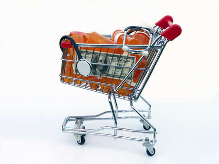 Miniature shopping cart isolated on white filled with prescription bottles, a US one hundred dollar bill and a stethoscope illustrating the high cost of prescriptions. 写真素材