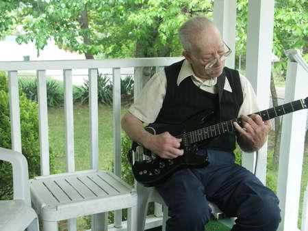front porch: Ancianos caballero tocar la guitarra en su porche delantero. Focus on intencional cara con movimiento borroso en las manos.