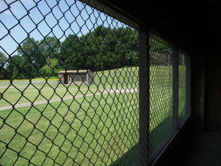 baseball dugout: Looking out of a baseball dugout at an empty field. Stock Photo