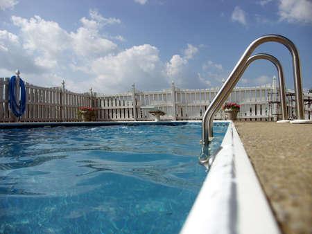 inground: Ladder and diving board of an inground pool. Focus on ladder.