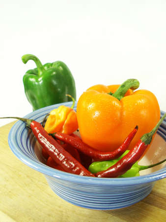 peppers hot and sweet in a bowl on a cutting board with white background