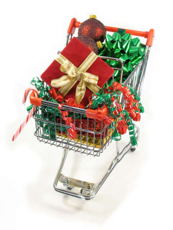 Christmas packages, ornaments candy cane and a bow in a miniature shopping cart. photo