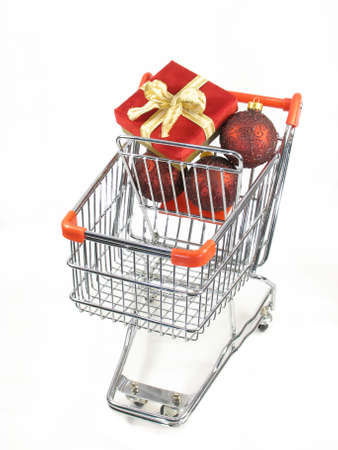 A christmas package with ornaments in a miniature shopping cart. Stock Photo