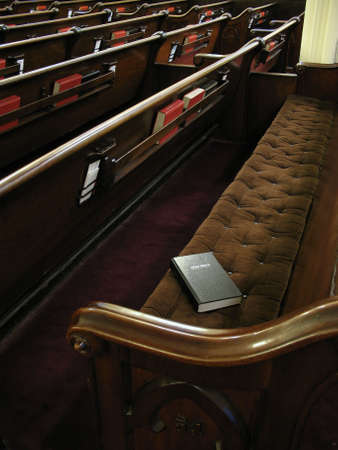 pew: Bible on empty pew. Focused on bible. Empty church with lots of pews. Stock Photo