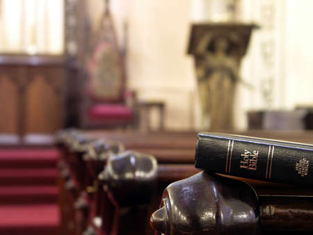 Bible resting on the back of a church pew. Shallow DOF with sharp focus on bible. Stock Photo