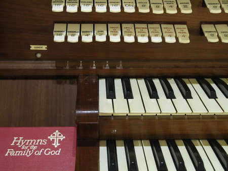 Hymnal resting beside a church organ. Stock Photo - 741825