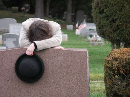 bereavement: Young woman grieving at graveside.
