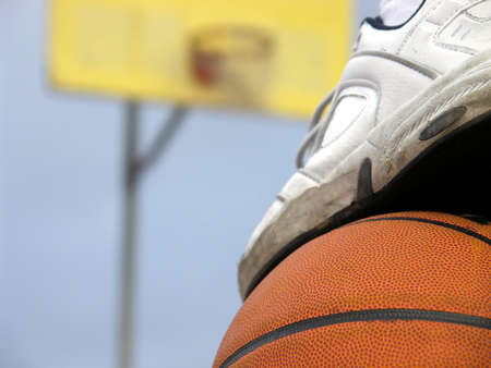 A foot on top of a basketball with out-of-focus hoop in background.