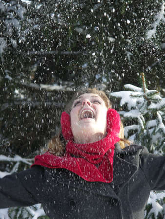 Beautiful blond girl throwing snow into the air. photo