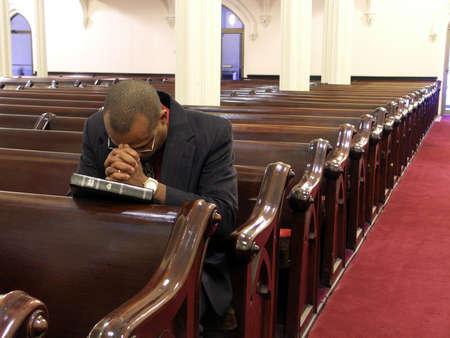 hymnal: Afro-americano uomo pregare da solo.