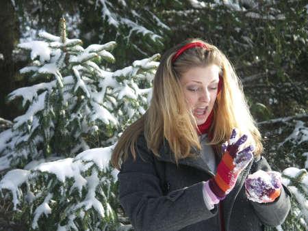 Beautiful blond girl making a snowball. photo
