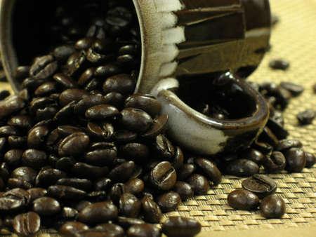 tissu or: Brown tasse � caf� avec des grains de caf� d�versant hors de l'or sur un chiffon.