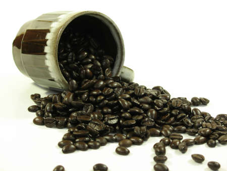 Brown coffee mug with coffee beans spilling out of it on white. Stock Photo - 753902