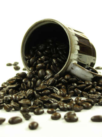Brown coffee mug with coffee beans spilling out of it on white. Stock Photo - 753900