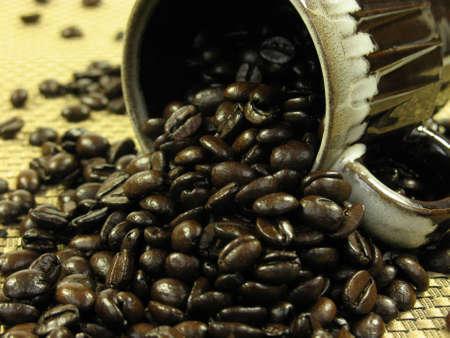 tissu or: Brown tasse � caf� avec des grains de caf� de r�pandre sur un tissu d'or.
