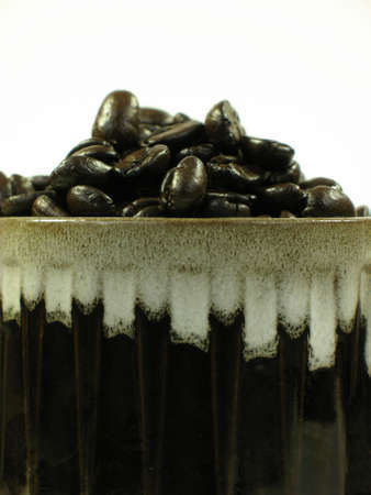 Close up of brown coffee mug with coffee beans on white. Stock Photo - 753893