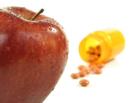 apple and pills spilling out of bottle on white. Stock Photo