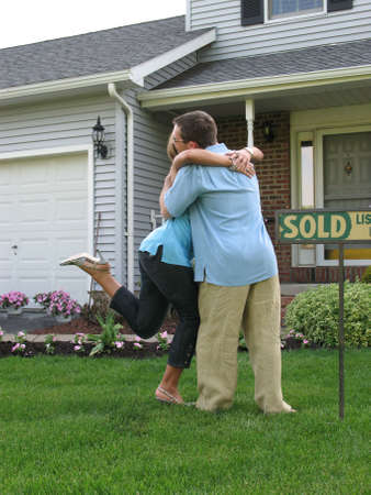 purchased: Couple hugging outside of newly purchased house