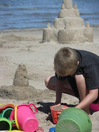 Un ni�o construye un castillo de arena en la playa.  Foto de archivo - 1483190