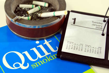 Cigarette in ashtray with stop smoking literature on calendar open to January 1st.