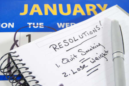 A calendar opened to January with the first circled, a notebook with two New Year's resolutions written out.