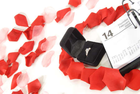 Engagement ring in box near calendar open to Febuary 14th surrounded by a heart of rose petals with more rose petals in background.