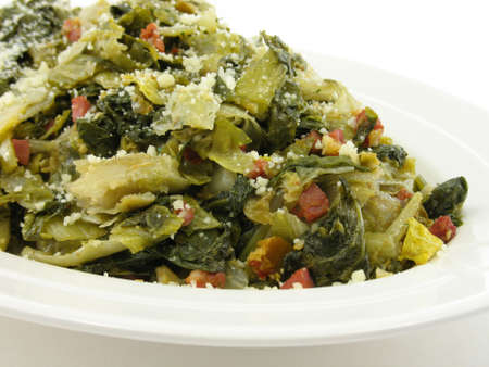 Mixed cooked greens on a white plate isolated on white.