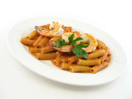 Shrimp over rigatoni in a red sauce on a white plate isolated on white