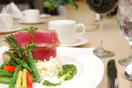 Tuna steak on a white plate isolated on a restaurant table. photo